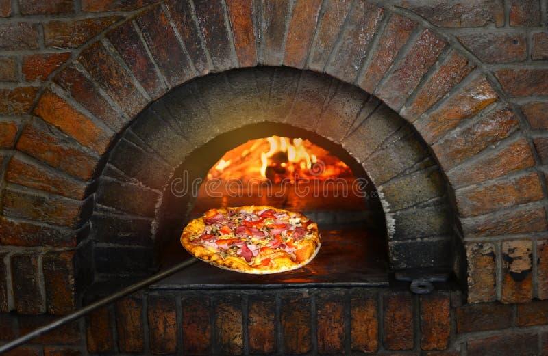 在石火炉附近的比萨与火 传统意大利比萨店餐馆 库存照片