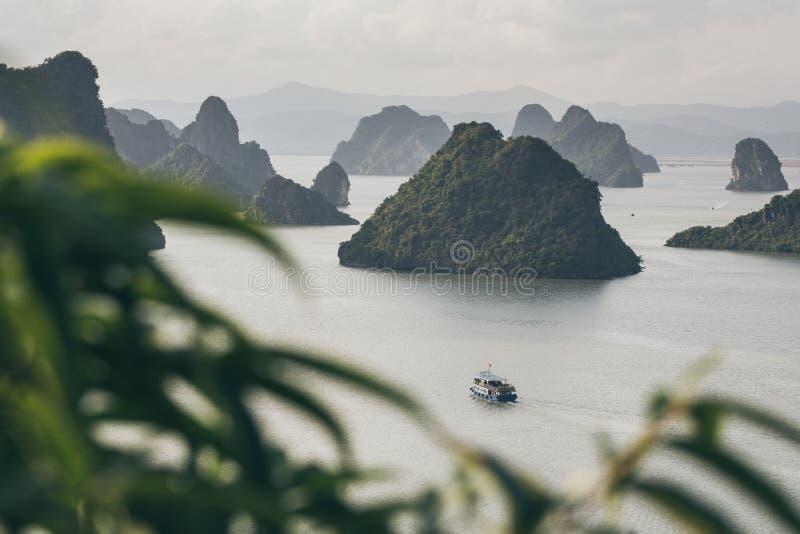 在石灰石山中的旅游游轮航行在下龙湾,越南 库存图片