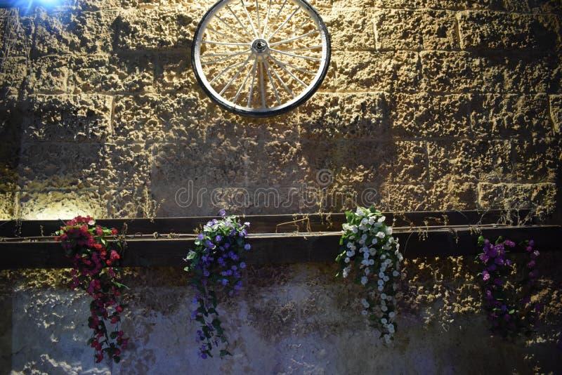 在石砖黄色墙壁上的自行车车轮在晚上以色列,迪莫纳, `平均观测距离`, 2018年 免版税库存照片