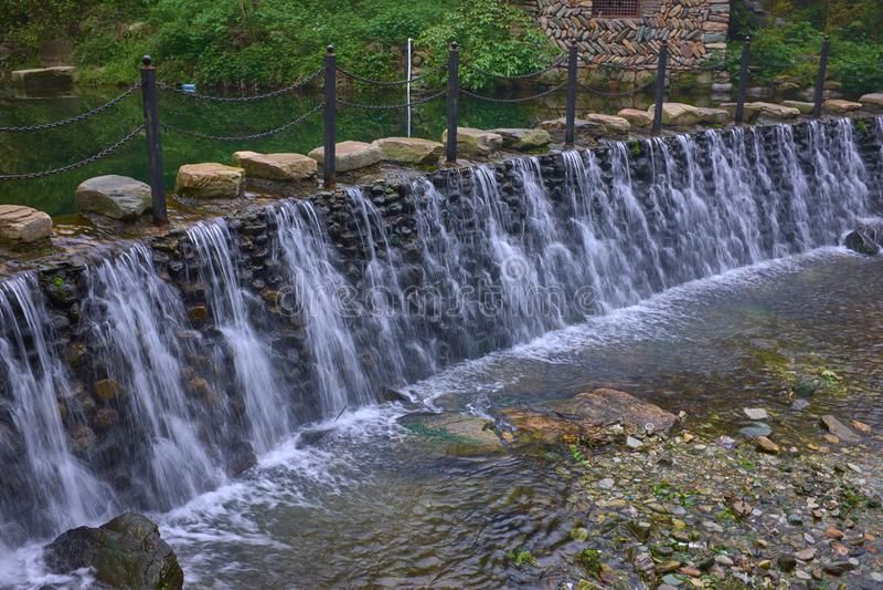 在石路下的美丽的瀑布在山 免版税库存照片