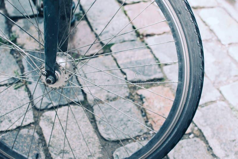 在石路面背景的自行车轮子  图库摄影