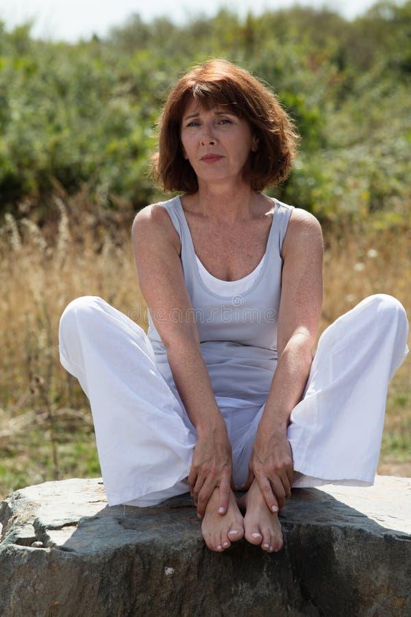 在石头的哀伤的成熟瑜伽妇女选址户外 图库摄影