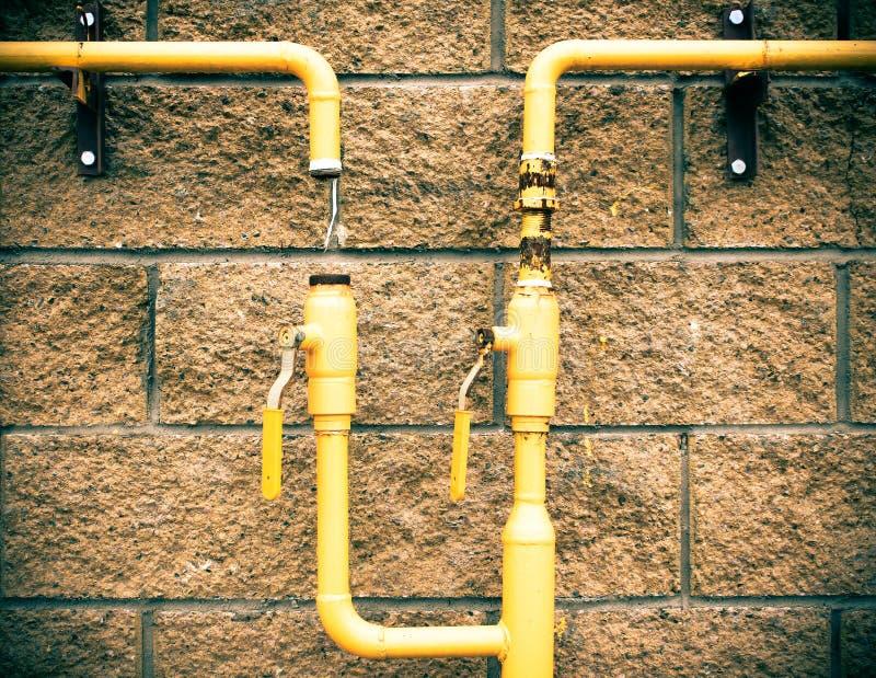 在石头的黄色煤气管 砖墙 免版税图库摄影