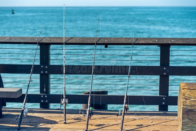 在码头、蓝色海和天空蔚蓝背景的钓鱼竿 库存图片