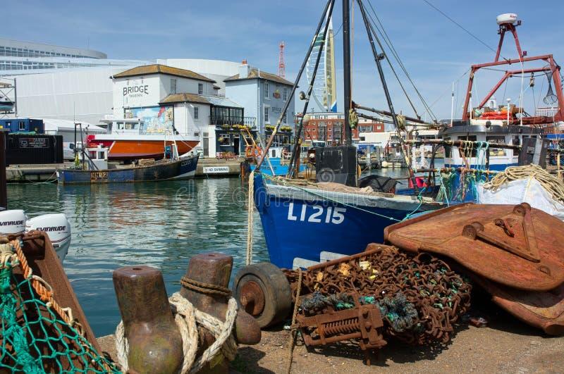在码头区的被停泊的渔船 网&清疏的链子 图库摄影