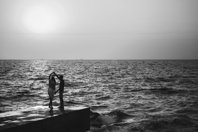 在码头的年轻夫妇跳舞在海滩夏时 图库摄影