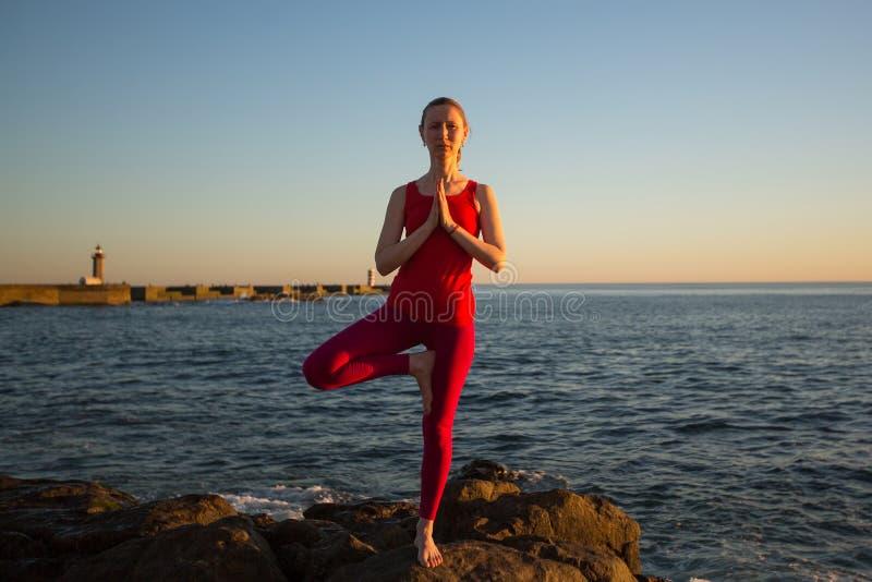 在码头的年轻女人实践的瑜伽在海附近 库存图片
