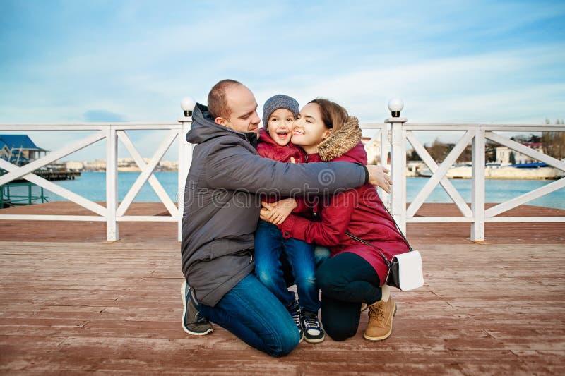 在码头的愉快的家庭在海附近一起在一个晴天 免版税图库摄影