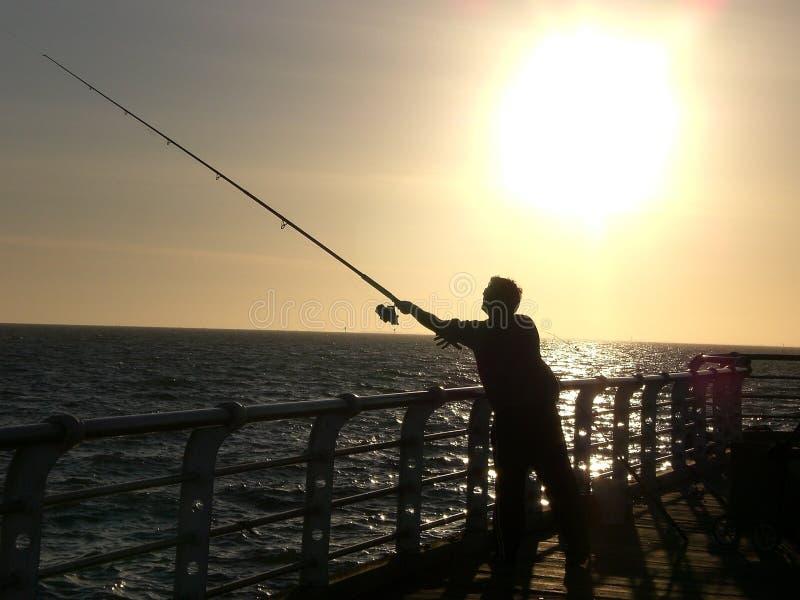 在码头的日落钓鱼 免版税库存图片