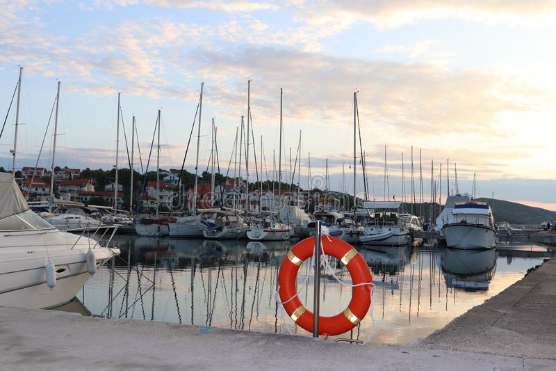 在码头的橙色救生圈在反对航行背景的克罗地亚小游艇船坞乘快艇 在水和挽救drownin的安全 库存图片