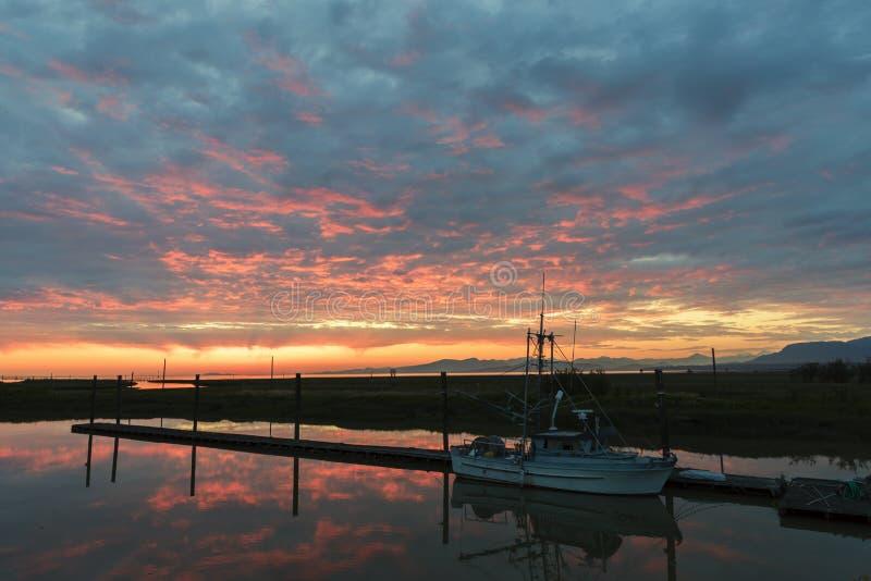 在码头的渔船在有反射的码头在反对平衡的天空的水中,在与焕发和云彩的黄昏 库存照片