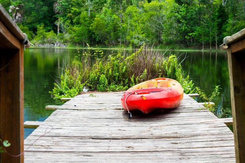 在码头的皮船有湖和树的 免版税库存照片