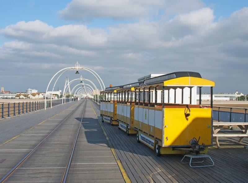 在码头的黄色火车在southport默西赛德郡在与镇大厦的一个明亮的夏日反对蓝色多云天空 免版税库存照片