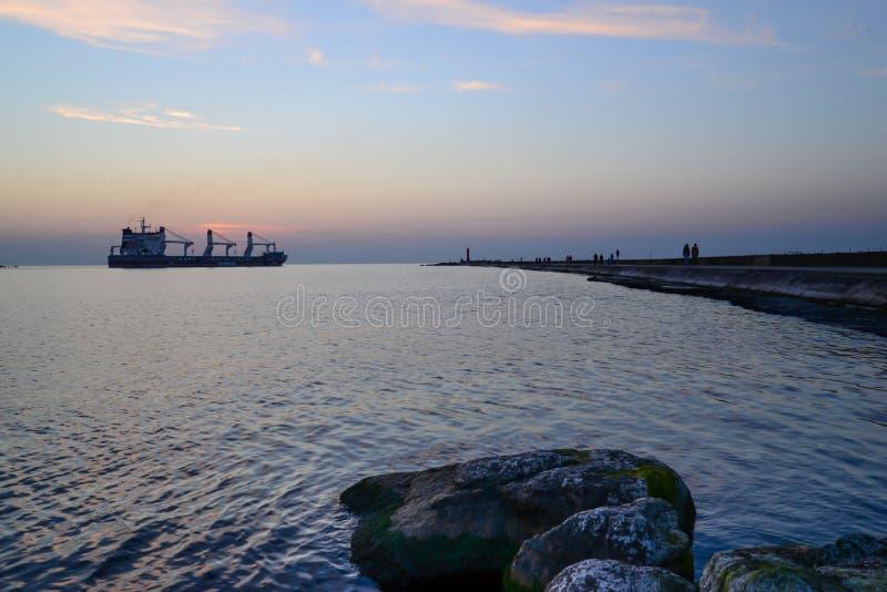 在码头和一艘通过的船的日落 免版税库存图片