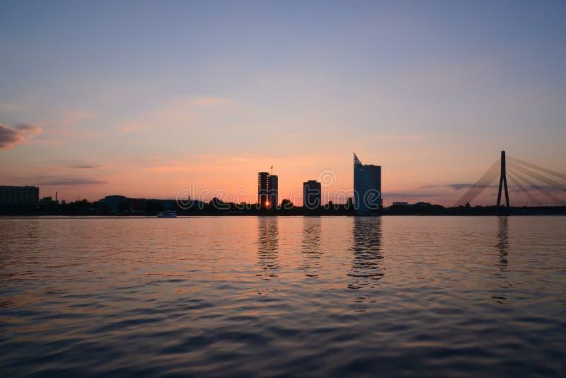 在码头的日落-通过大厦晒黑光芒 库存图片