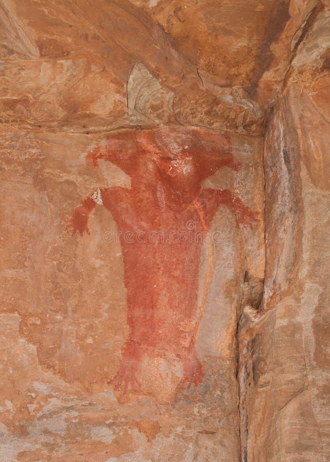 在砂岩墙壁上的印地安人象形文字在突出物下在南部的犹他沙漠 库存照片