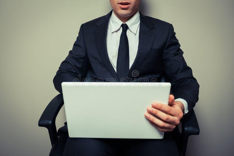 在研究膝上型计算机的办公室椅子的商人 图库摄影