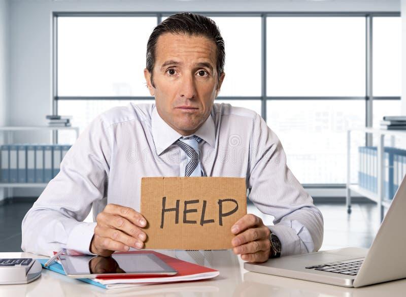 在研究计算机膝上型计算机的危机的绝望资深商人在重音的办公桌在压力下 免版税库存图片