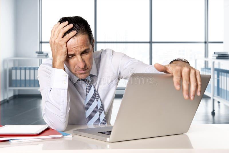 在研究计算机膝上型计算机的危机的绝望资深商人在重音的办公桌在压力下 库存图片