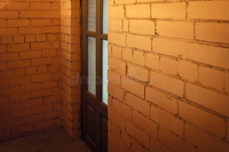 在砖后的顶楼门 免版税库存图片