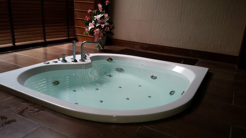 在砖地上的浴缸用在卫生间的水 免版税图库摄影