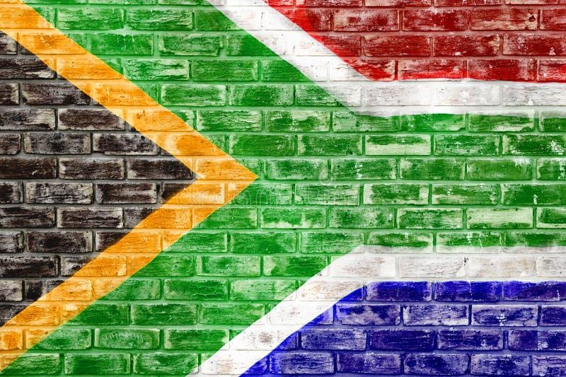 在砖墙上的南非旗子 库存例证