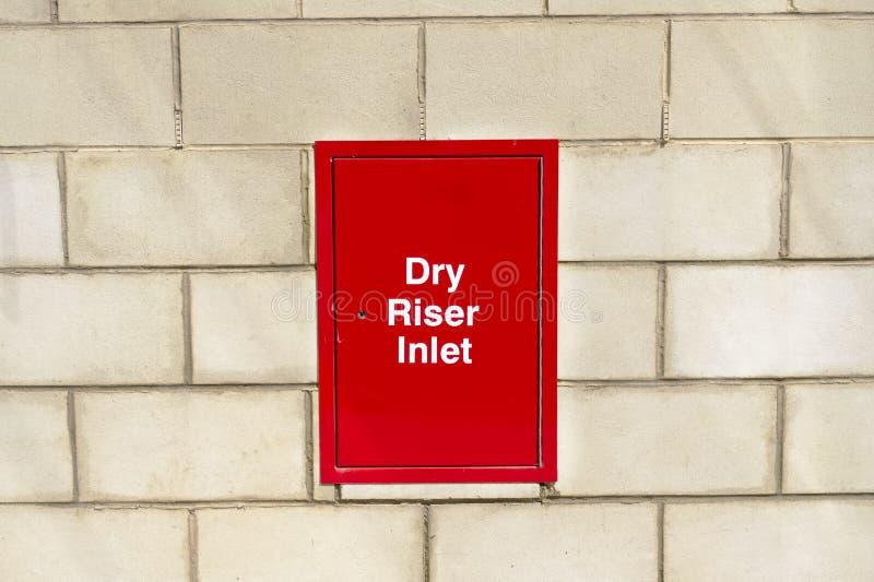 在砖墙上的干燥造反者入口箱子红色紧急消防部门的浇灌水管旅团引擎的连接在商城零售 免版税库存图片