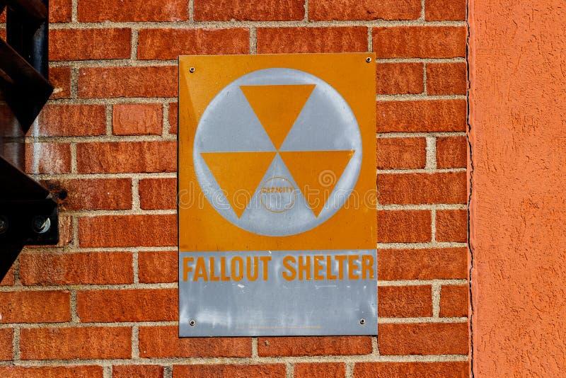 在砖墙上的橙色`防核尘地下室`标志我 免版税库存图片