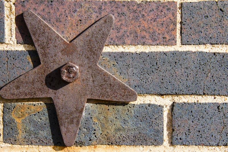 在砖墙上的生锈的星 免版税库存照片