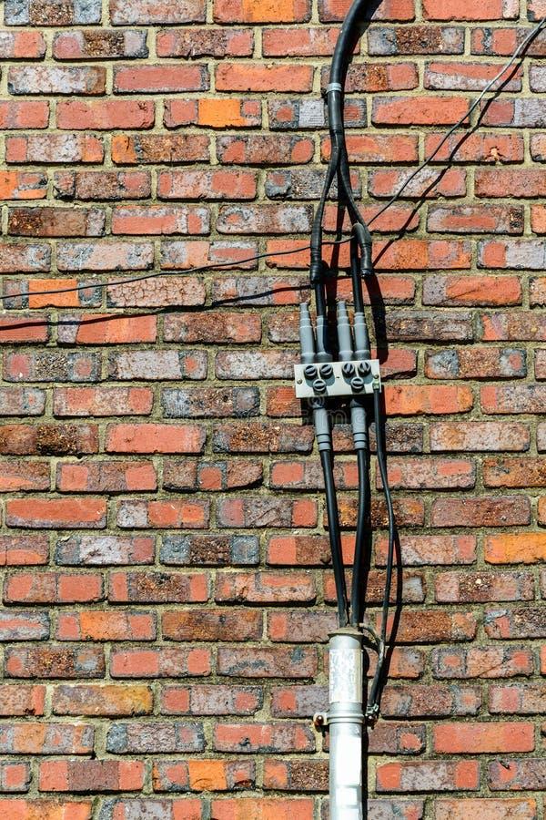 在砖墙上的电导线 免版税库存照片