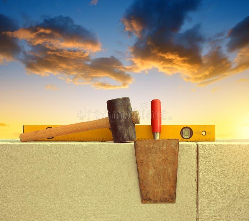 在砖墙上的石工工具 库存照片