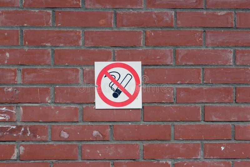 在砖墙上的禁烟标志 免版税库存照片