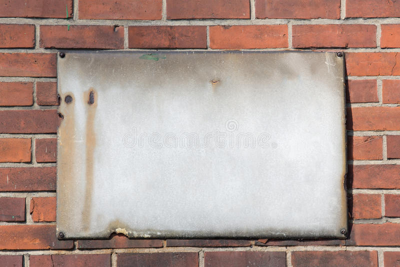 在砖墙上的空白的减速火箭的生锈的金属标志 免版税库存照片