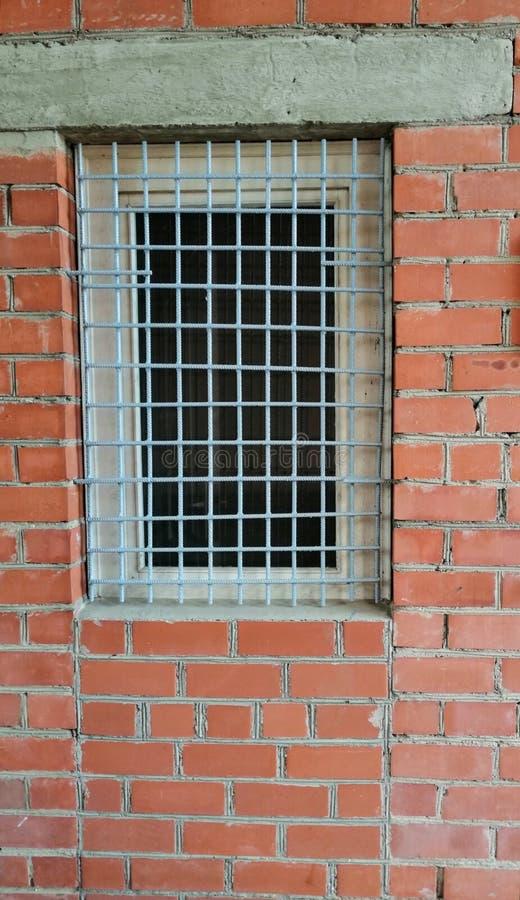 在砖墙上的窗口格栅 免版税库存照片