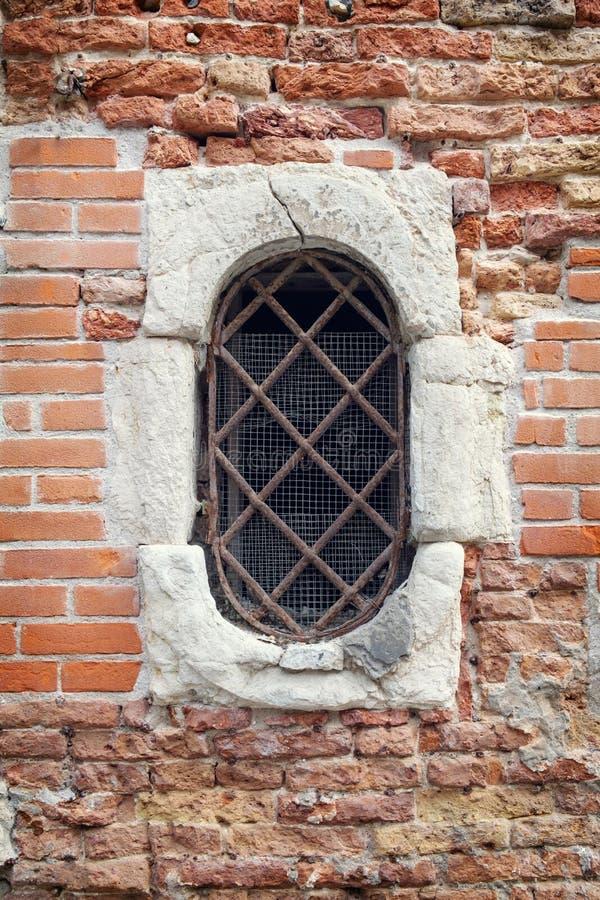 在砖墙上的老装门的窗口 库存图片