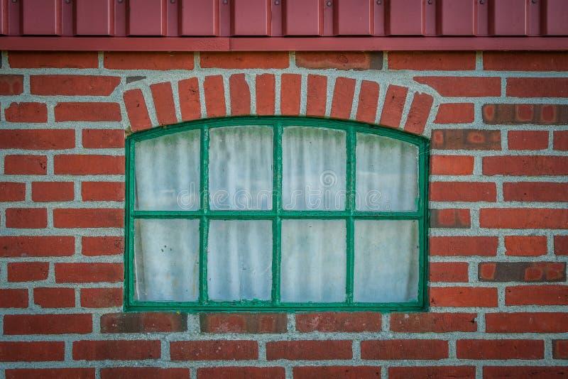 在砖墙上的绿色窗口 免版税图库摄影
