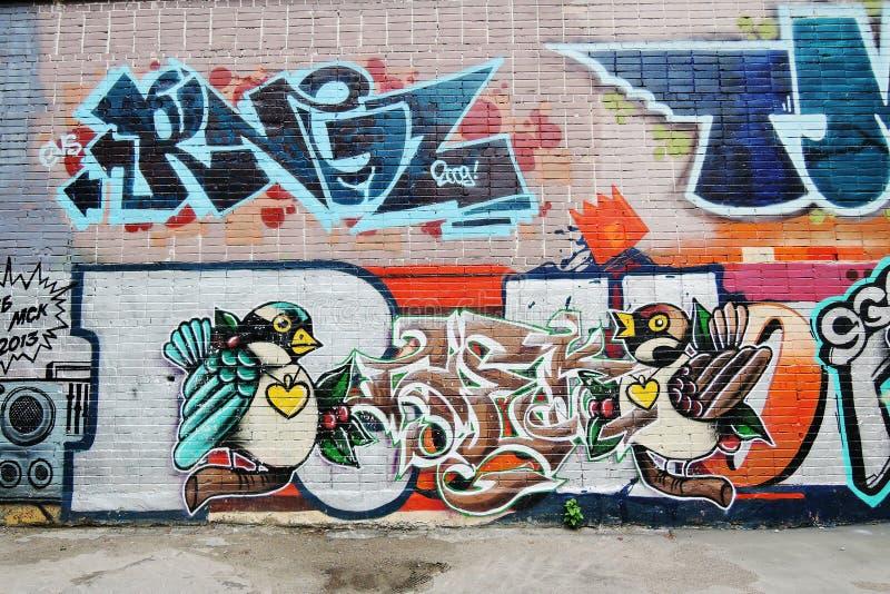 在砖墙上绘的两只鸟 向量例证