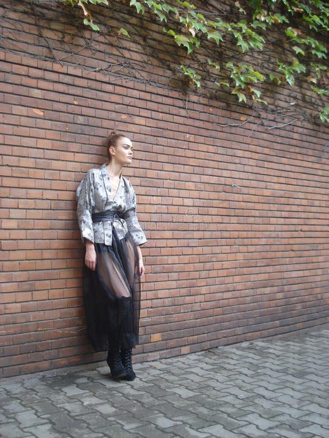 在砖墙前面的女性在内在庭院里 免版税库存图片