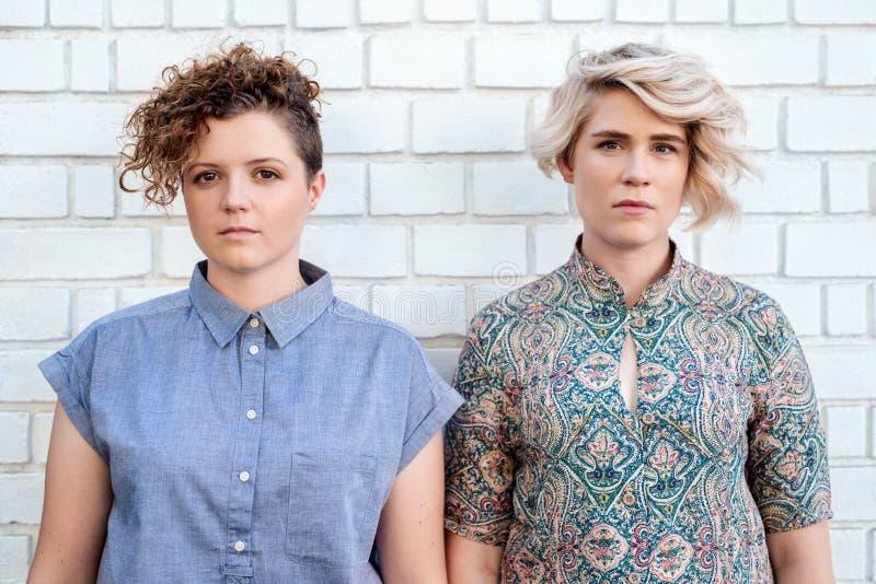 在砖墙前面的年轻女同性恋的夫妇身分 免版税图库摄影
