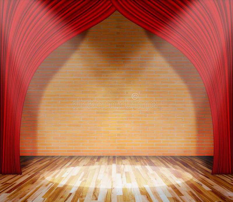 在砖墙和木地板前面的红色帷幕与照明设备 库存照片