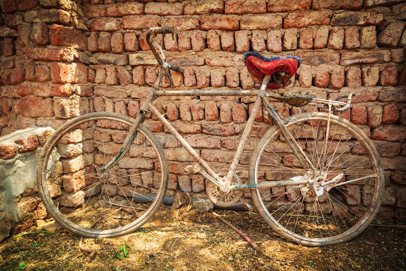 在砖墙的多灰尘的老自行车 库存照片