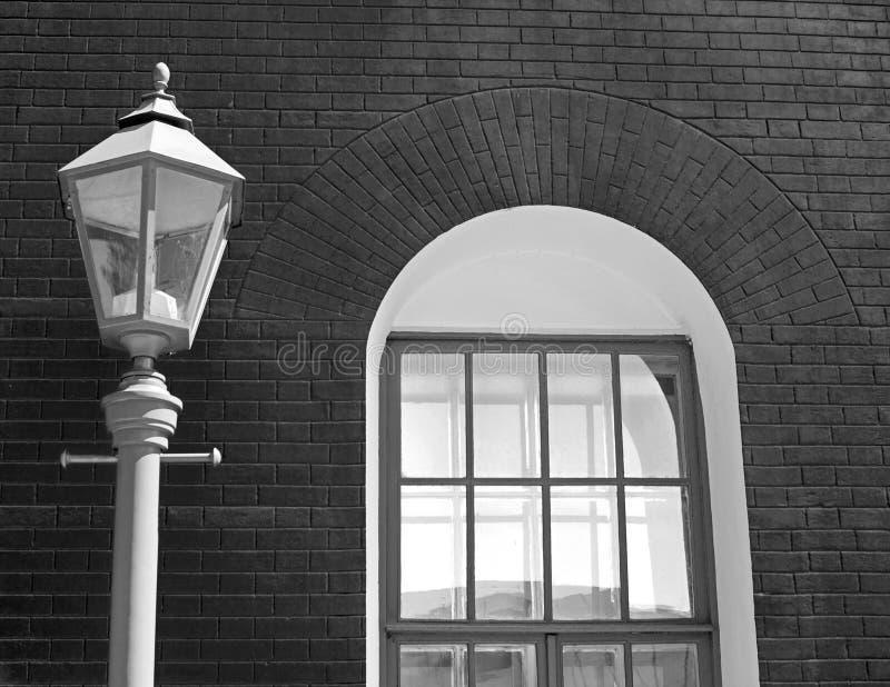 在砖墙的背景的葡萄酒老街灯太阳和一个白色窗口的点燃的一个老大厦 免版税库存照片