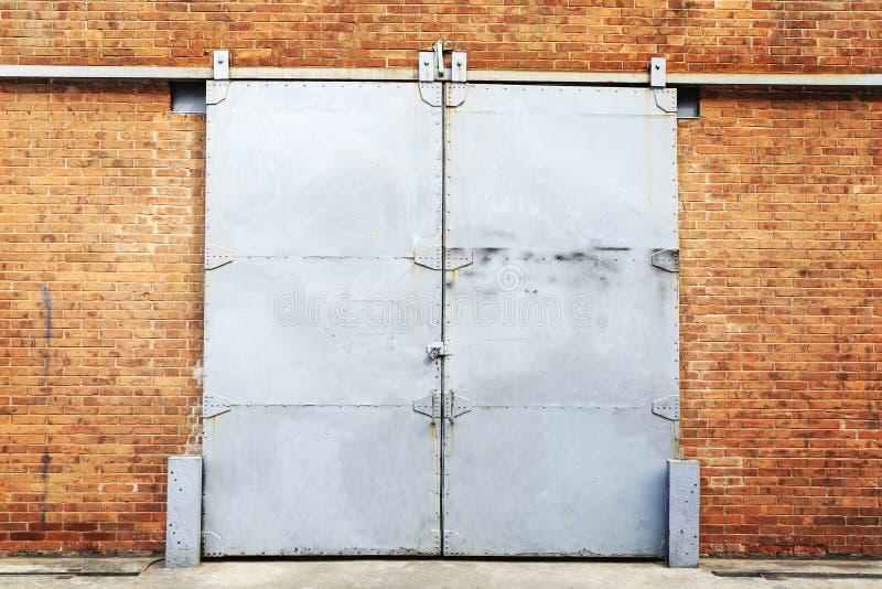 在砖墙的金属滚滑门 库存照片