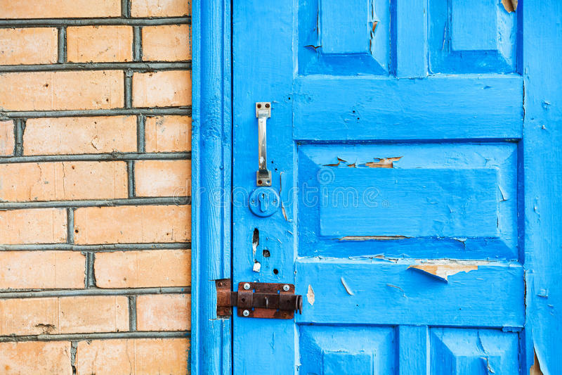 在砖墙的闭合的破旧的蓝色木门 库存图片