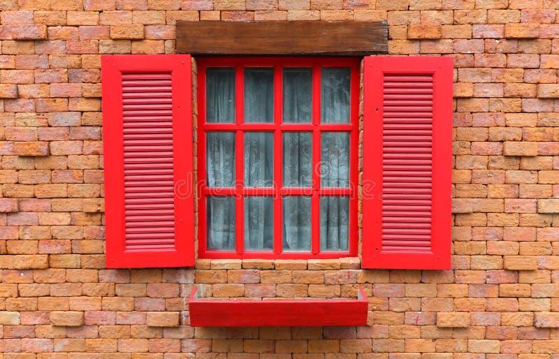 在砖墙纹理背景的红色木窗口 免版税图库摄影