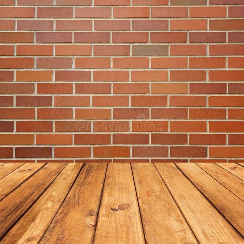 在砖墙背景的木甲板地板 免版税库存照片