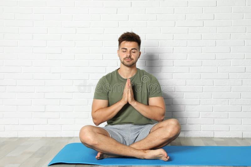 在砖墙附近的年轻人实践的禅宗瑜伽 库存照片