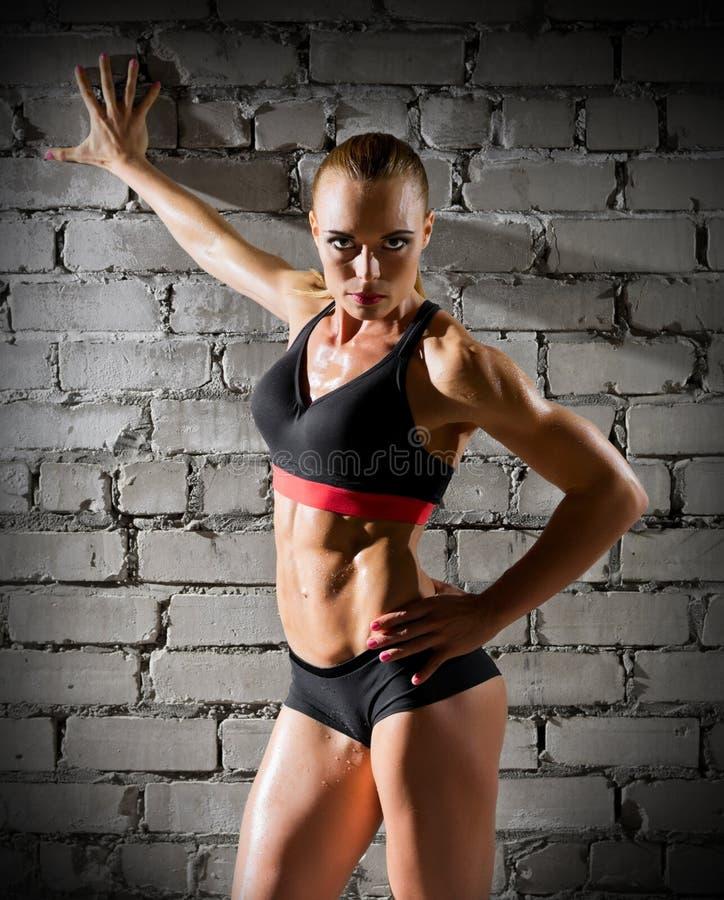 在砖墙(正常版本)上的肌肉妇女 免版税库存照片