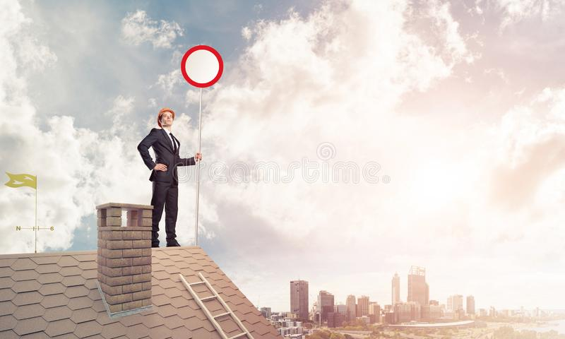 在砖房子屋顶陈列中止路标的白种人商人 免版税库存图片
