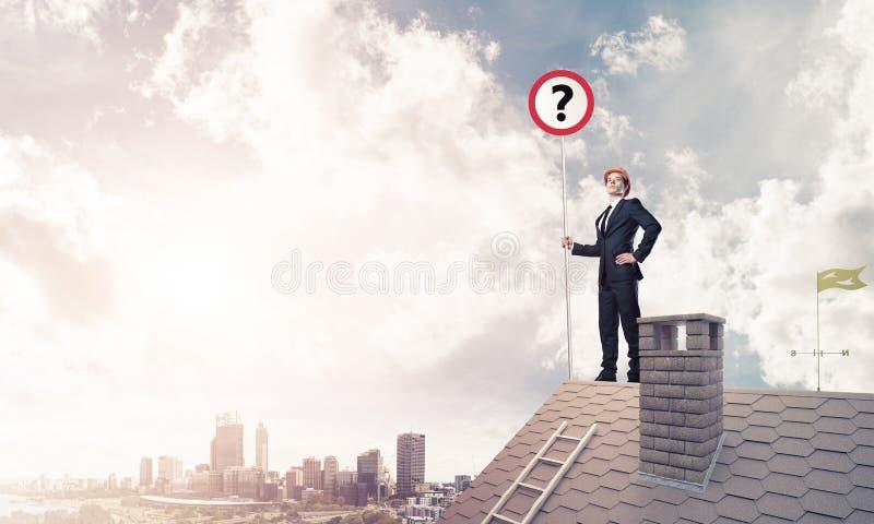 在砖房子屋顶陈列横幅的商人与问题3月 免版税库存图片